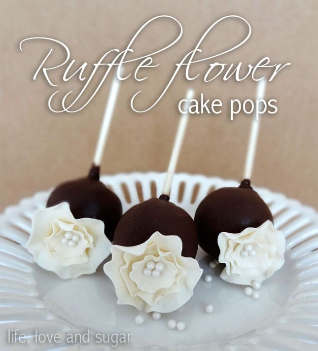 Three flower cake pops on a white plate