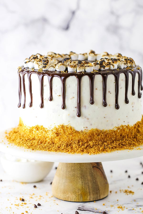 close up of whole cake on cake stand - white marshmallow frosting, graham crumbs around bottom and chocolate ganache drip with toasted marshmallows on top