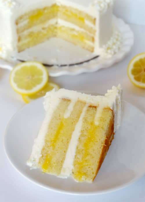A slice of Triple Lemon cake on a white plate surrounded by lemons and the whole cake behind it