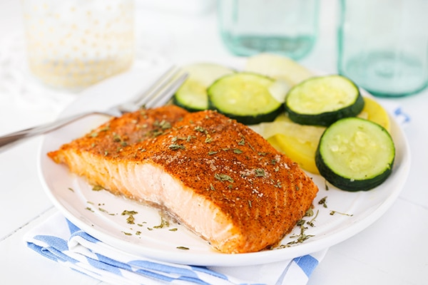 horizontal image of Easy Creole Salmon on white plate with veggies