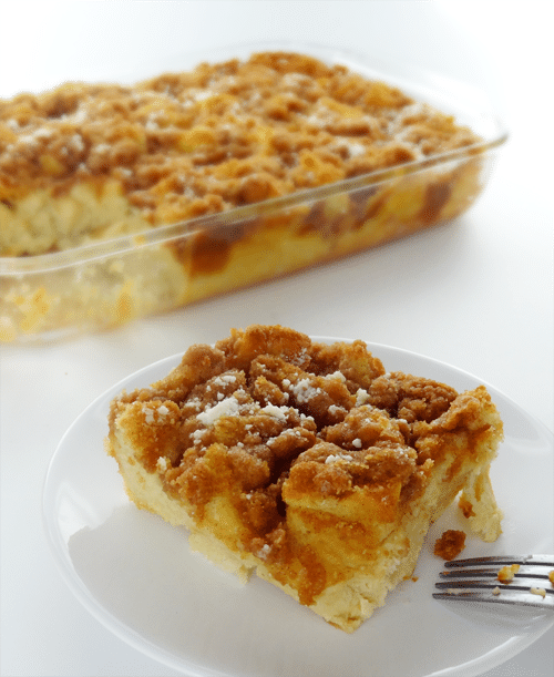 A piece of Cinnamon Brown Sugar French Toast Casserole on a white plate with the rest of the casserole behind it