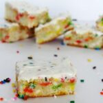 A Funfetti Blondie with icing surrounded by sprinkles