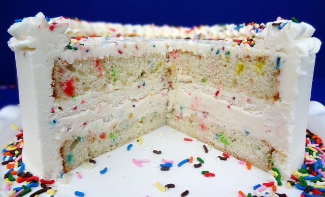 Side view of a cut Funfetti Cake Batter Ice Cream Cake so you can see the ice cream and sprinkles in the middle