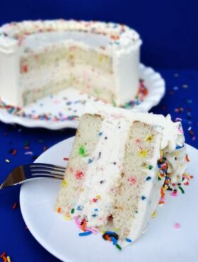 A slice of Funfetti Ice Cream Cake on white plate with the rest of the cake behind it