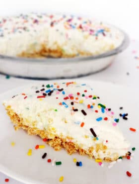 A slice of Funfetti Cake Batter Ice Cream Pie on a white plate with sprinkles