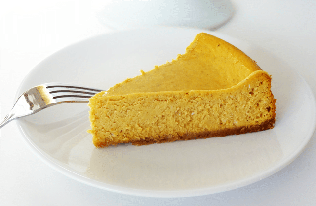 A Piece of Pumpkin Cheesecake on a White Plate with a Fork