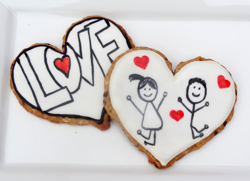 Two Heart-Shaped Oatmeal Cut-Out Cookies Decorated with Hearts and Stick Figures