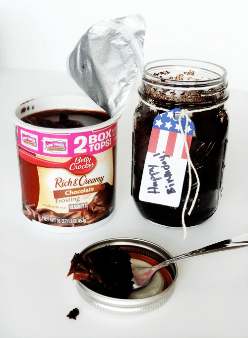 An open mason jar filled with cake next to an open container of chocolate frosting
