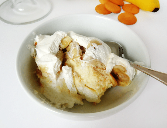 Close up of Banana Pudding with vanilla wafers and cool whip in white bowl with a spoon