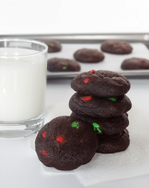 Chocolate Peanut Butter M&M Cookies are stacked next to a glass of milk with more cookies on a baking pan behind them