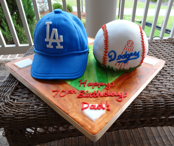 An LA Dodgers Hat Cake and Baseball Cake on a Baseball Field Cake Stand