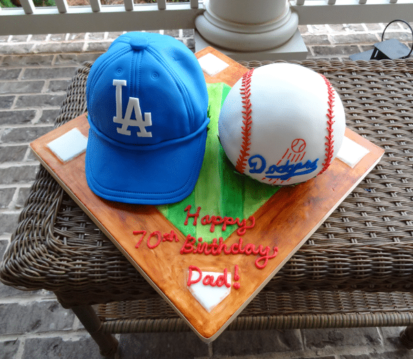 A Baseball Field Cake Stand Holding a Baseball Birthday Cake and a Dodgers Birthday Hat Cake