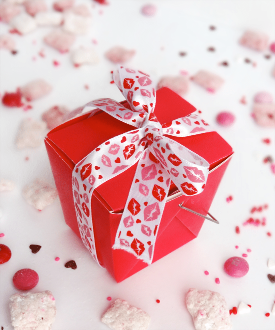 Puppy Chow sprinkled around a red Valentine's Day box