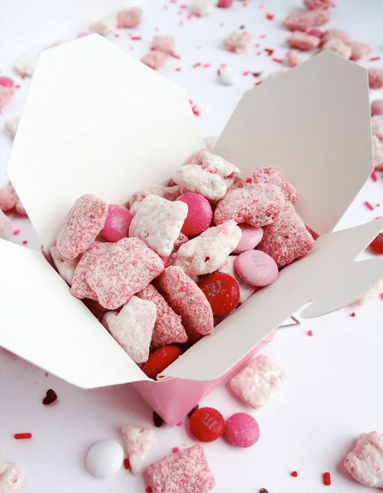 Pink and white Puppy Chow with M&ms in a takeout container