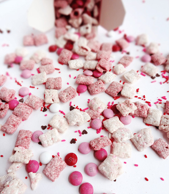 Strawberries and Cream Puppy Chow spilled out on a white surface