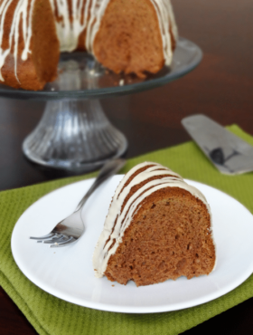 A slice of Bailey's Irish Cream Cake on a white plate with a fork