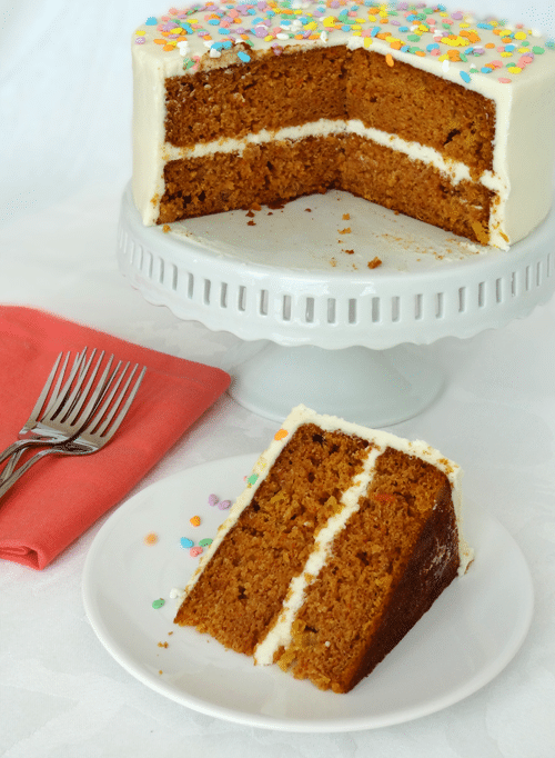 Super Moist Carrot Cake slice on white plate with cake on white stand in background