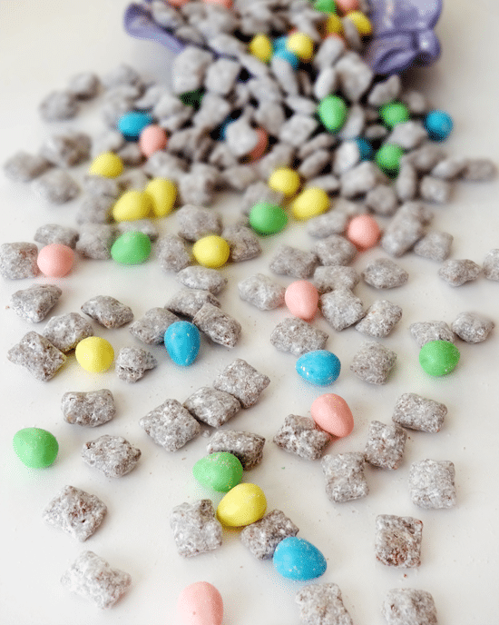 Muddy Buddies and Reese's Easter Eggs spilled out on a white surface