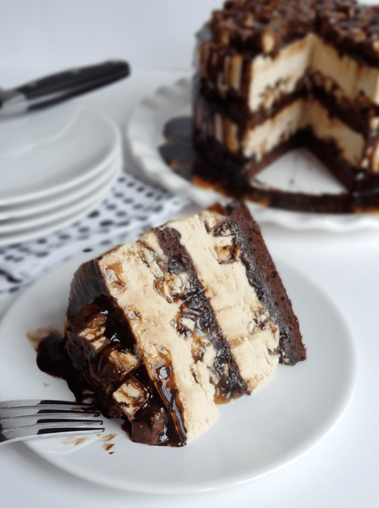A Slice of Snickers Cake on a White Plate in Front of a Stack of Other Plates