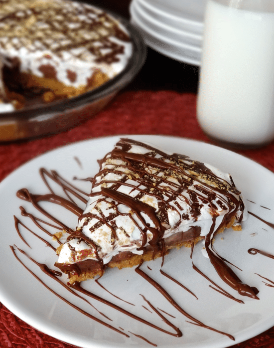 A slice of Peanut Butter Nutella and Marshmallow Pie on a white plate and drizzled with chocolate