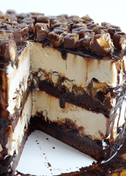 A Snickers Brownie Ice Cream Cake on a Cake Stand with a Slice Missing