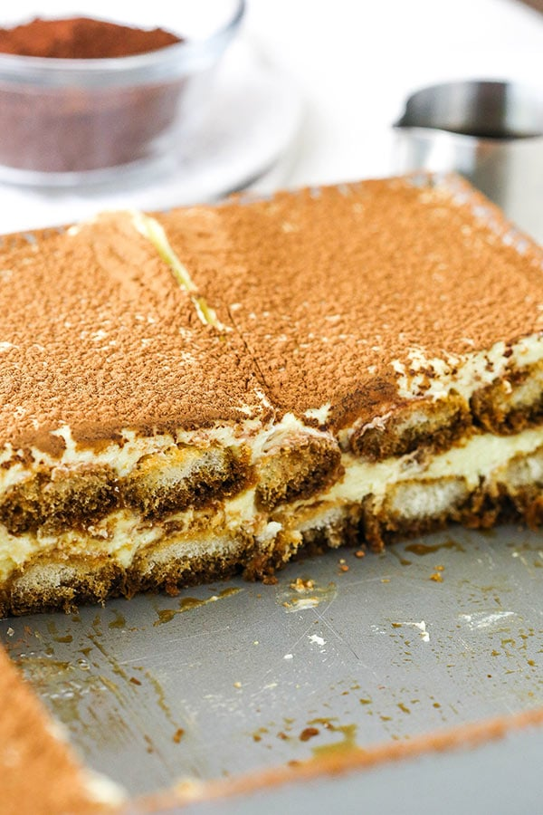 Tiramisu in a silver pan with a few slices cut out