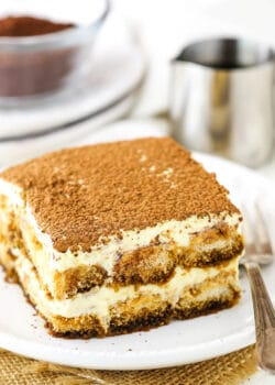 A piece of authentic Tiramisu on a white plate with a fork