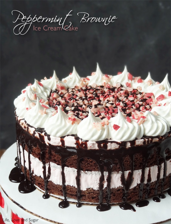 Peppermint Brownie Ice Cream Cake with fudge dripping down on a white platter