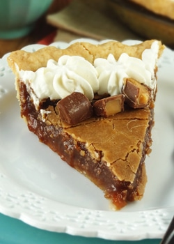 A slice of chocolate hazelnut chess pie with rolos on a white plate