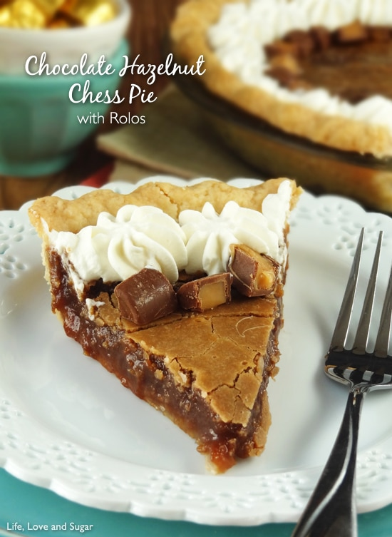 A slice of chess pie on a white plate is topped with whipped cream and Rolos