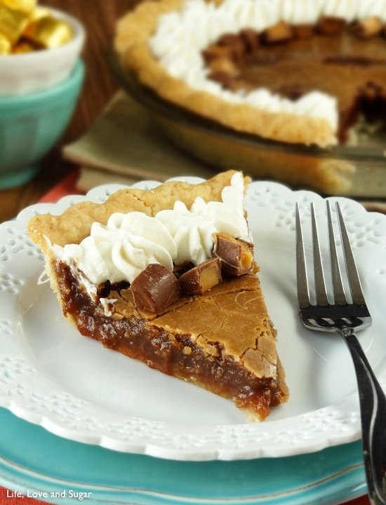A slice of Chocolate Hazelnut Chess Pie with Rolos and whipped cream on top sits on a white plate with a fork