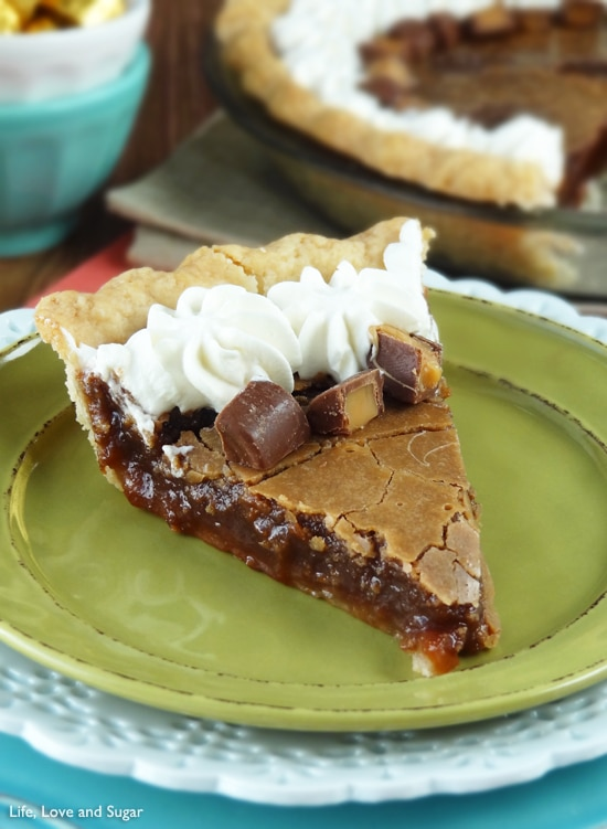 A slice of chocolate chess pie topped with whipped cream and Rolos sits on a green plate