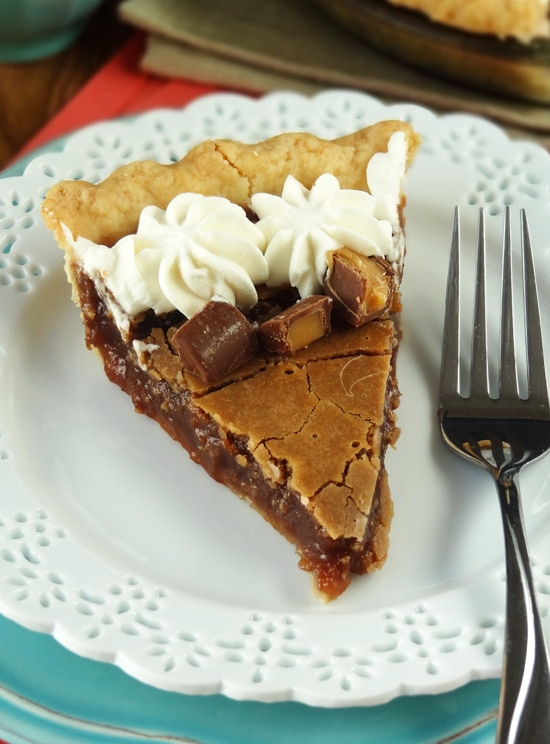 A fork and slice of chess pie sit on a white decorative plate