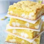 Lemon White Chocolate Gooey Bars stacked on wax paper