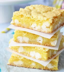 Lemon White Chocolate Gooey Bars stacked on wax paper
