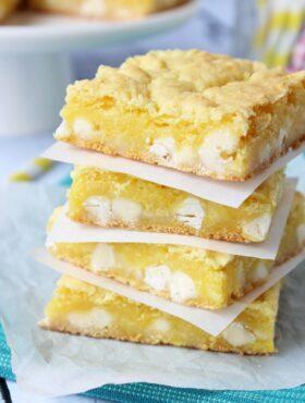Lemon White Chocolate Gooey Bars stacked on white plate