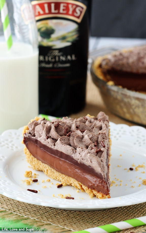 A slice of chocolate pie on a white plate with a bottle of Bailey behind it