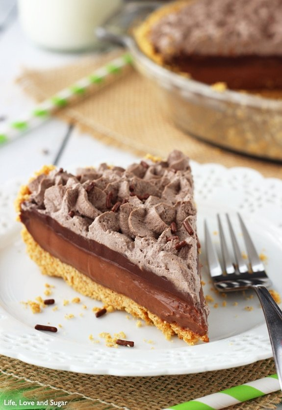 A slice of Baileys Chocolate Pie on a white plate with a fork