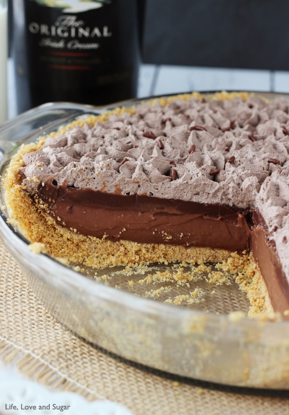 A glass dish filled with chocolate pie has a piece missing so you can see the layers of chocolate filling, ganache and whipped cream