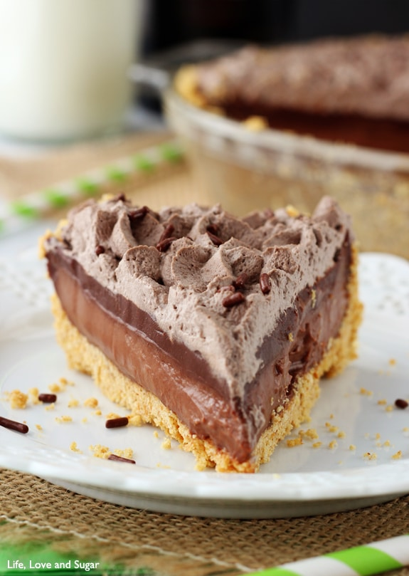 A slice of Chocolate Pie with layers of chocolate filling, ganache and whipped cream