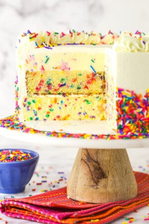 Funfetti millionaire cake with a slice cut out to show the layers