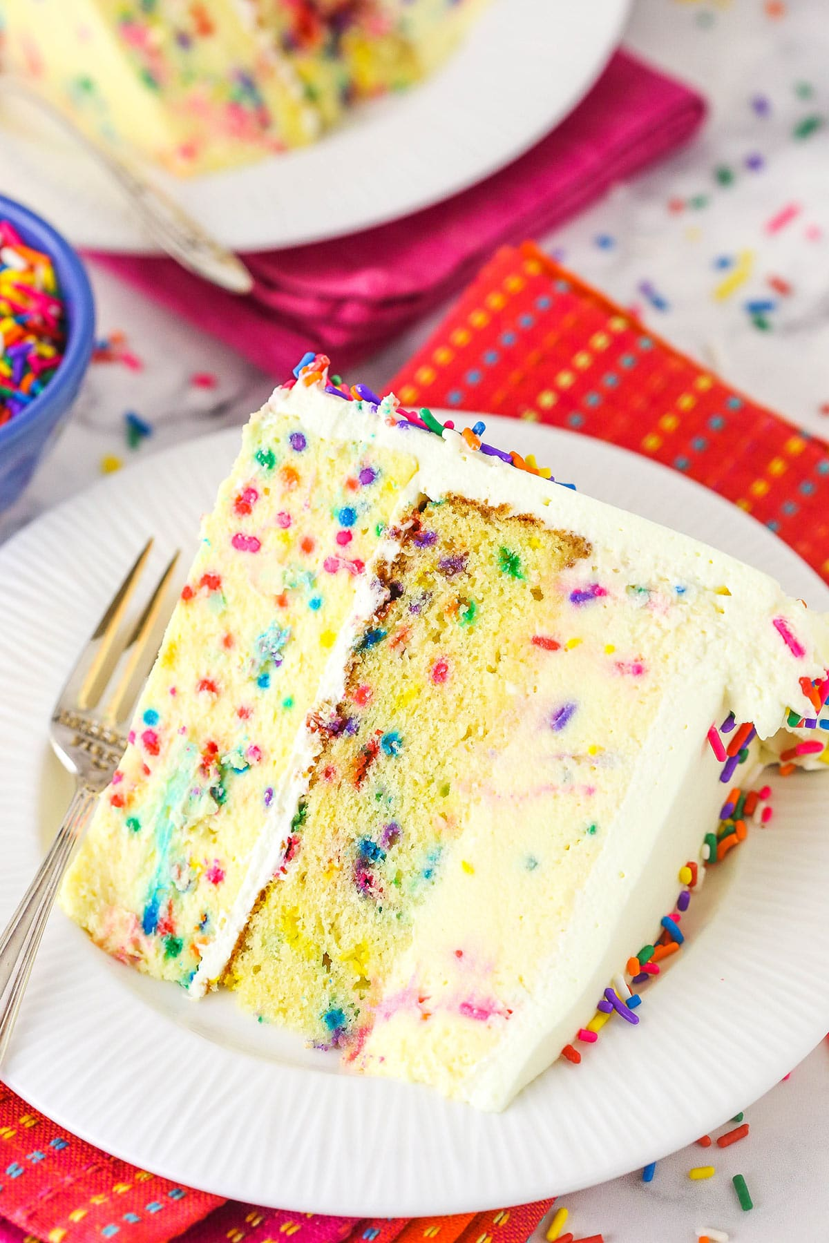 A slice of funfetti millionaire cake on a whit eplate