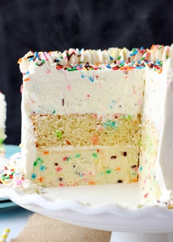 Funfetti Millionaire Cake slice on white stand with slice removed