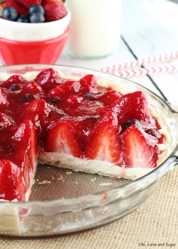 A Strawberry Cream Pie in a clear dish with a slice missing