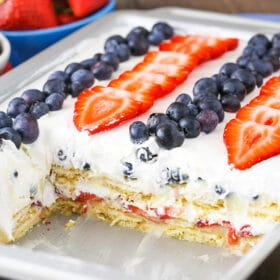 Strawberry and Blueberry Cheesecake Icebox Cake - layers of golden oreos, fresh berries, cheesecake pudding and whipped cream! No bake, delicious and perfect for July 4th!