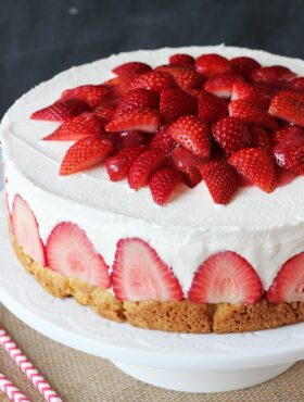A Strawberry Shortcake Cheesecake Topped with Fresh Strawberries Cut Into Quarters and Homemade Strawberry Sauce