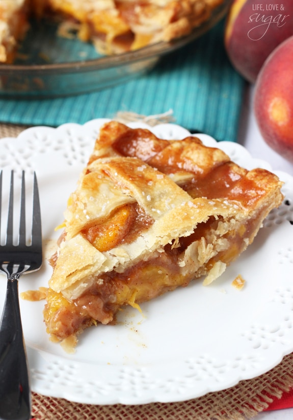 A big slice of Peach Pie with a fork on a white plate