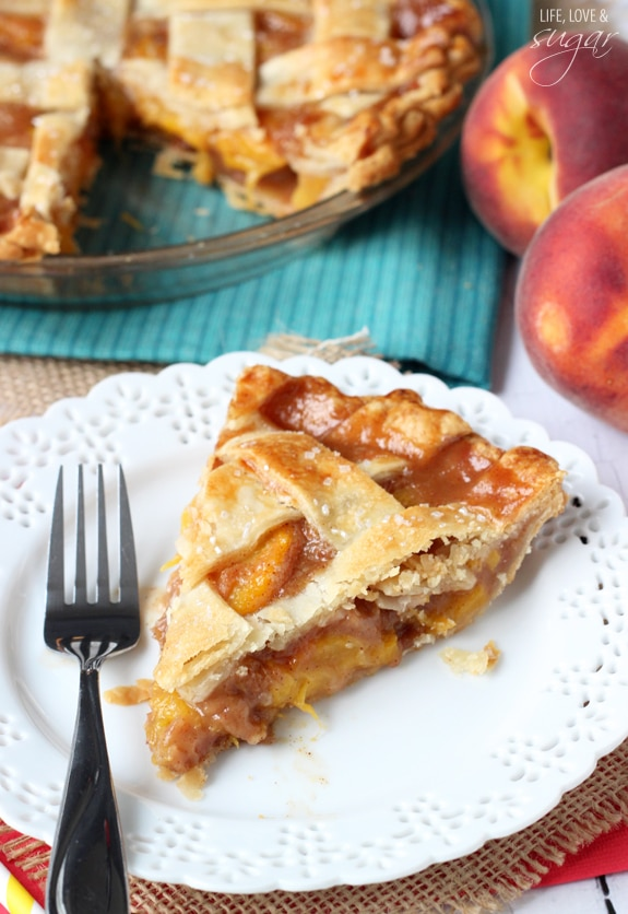 A fresh slice of Peach Pie on a plate with a fork