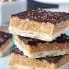 A Close-Up Shot of Three Stacked Chocolate Caramel Cookie Bars Topped with Sea Salt