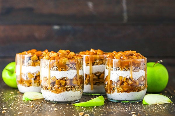 horizontal image of 4 caramel apple trifles on wood background